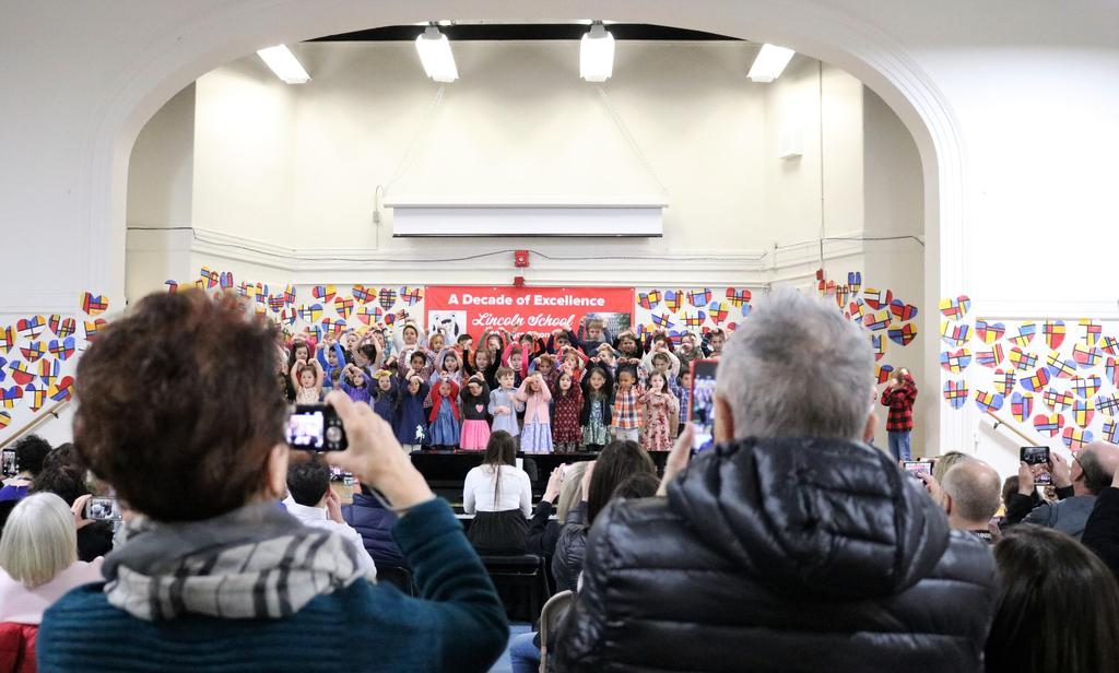 Photo of grandparents in audience using smart phones to record kindergartner performance.