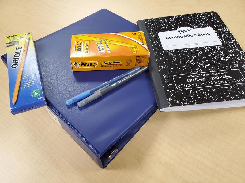 Various school supplies on a table: binder, composition notebook, pens, pencils, and highlighters