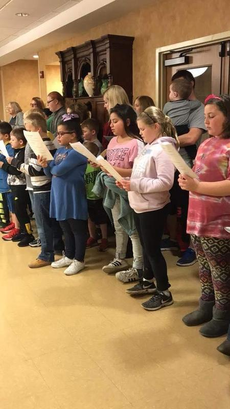 Students from Mrs. Greenberg's class and Mrs. Kendall's class singing Christmas carols