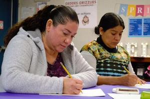 Geddes Elementary School parents practice self-portraits in the style of Frida Kahlo before trying their hand at five-line poems on March 21, as part of a 10-week art and poetry workshop.
