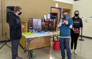 Students at the display table calling out raffle tickets