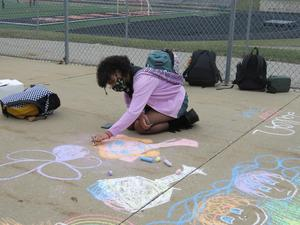 Students create chalk art drawings outside.