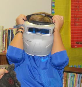 A student tries on a smaller welding helmet.