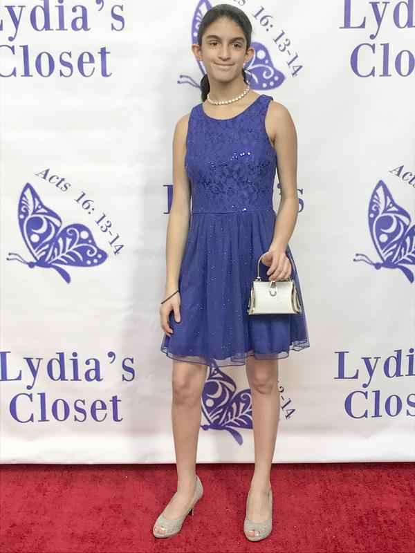 A student posing in front of the Lydia's Closet wall