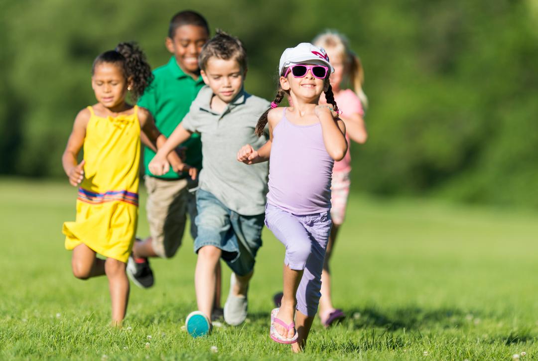 4 kindergarteners running on lawn