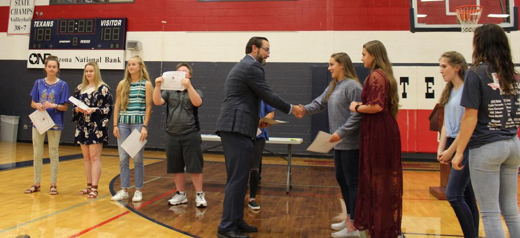 Alt 12th Grade All A's L-R Rallie Calhoun, Claire Coburn, Bayleigh Grogan, Greyson Fine pose with their academic achievement award while Principal Jason Valentine, congratulates Allie Messenger and Averie Messenger and Hayley Sloan and Zorina Weed await their award.