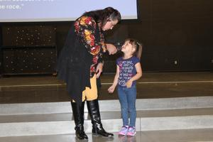 Administrator on stage with young child