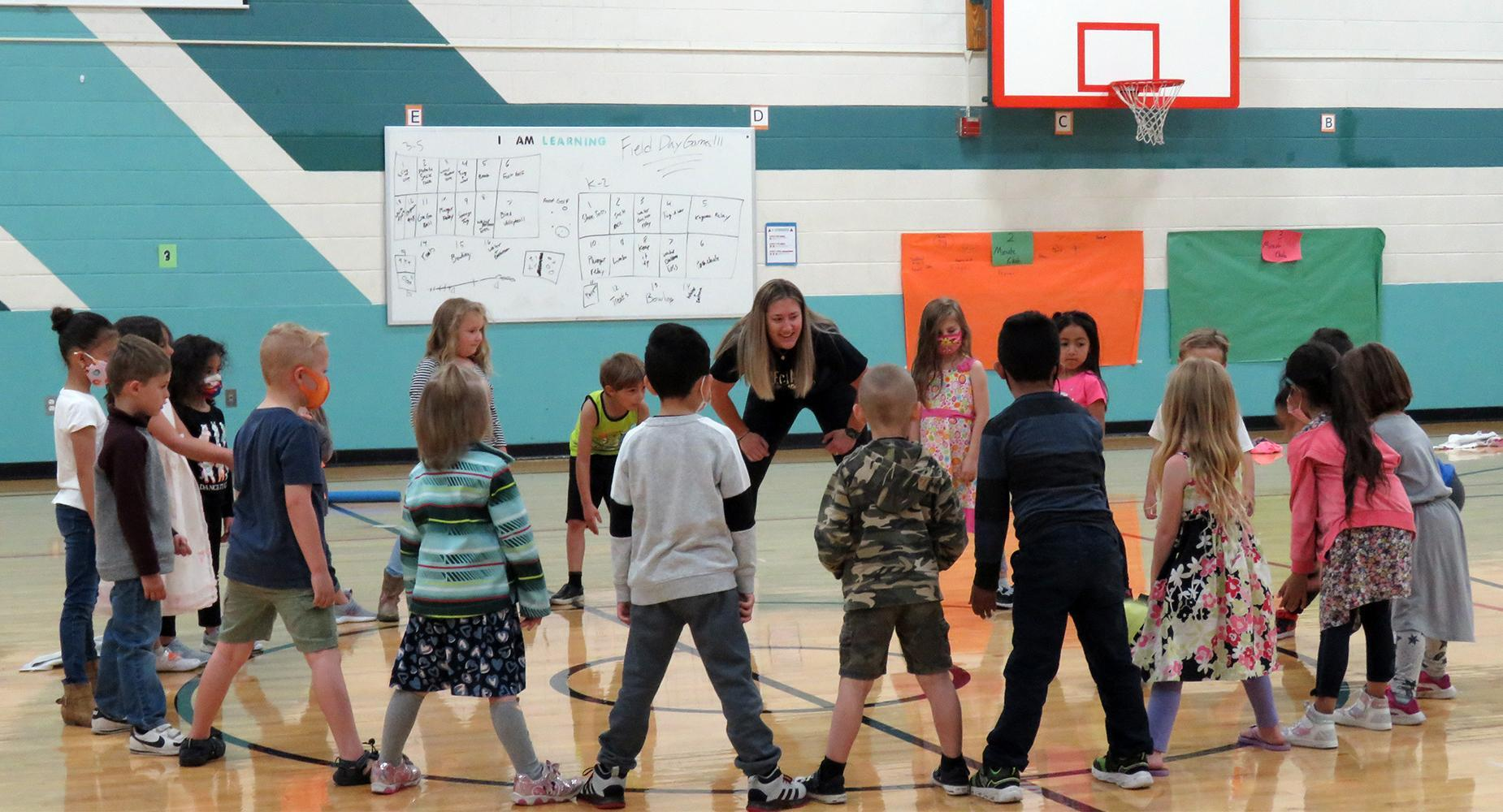 Young children in a circle with PE teacher, passing a ball