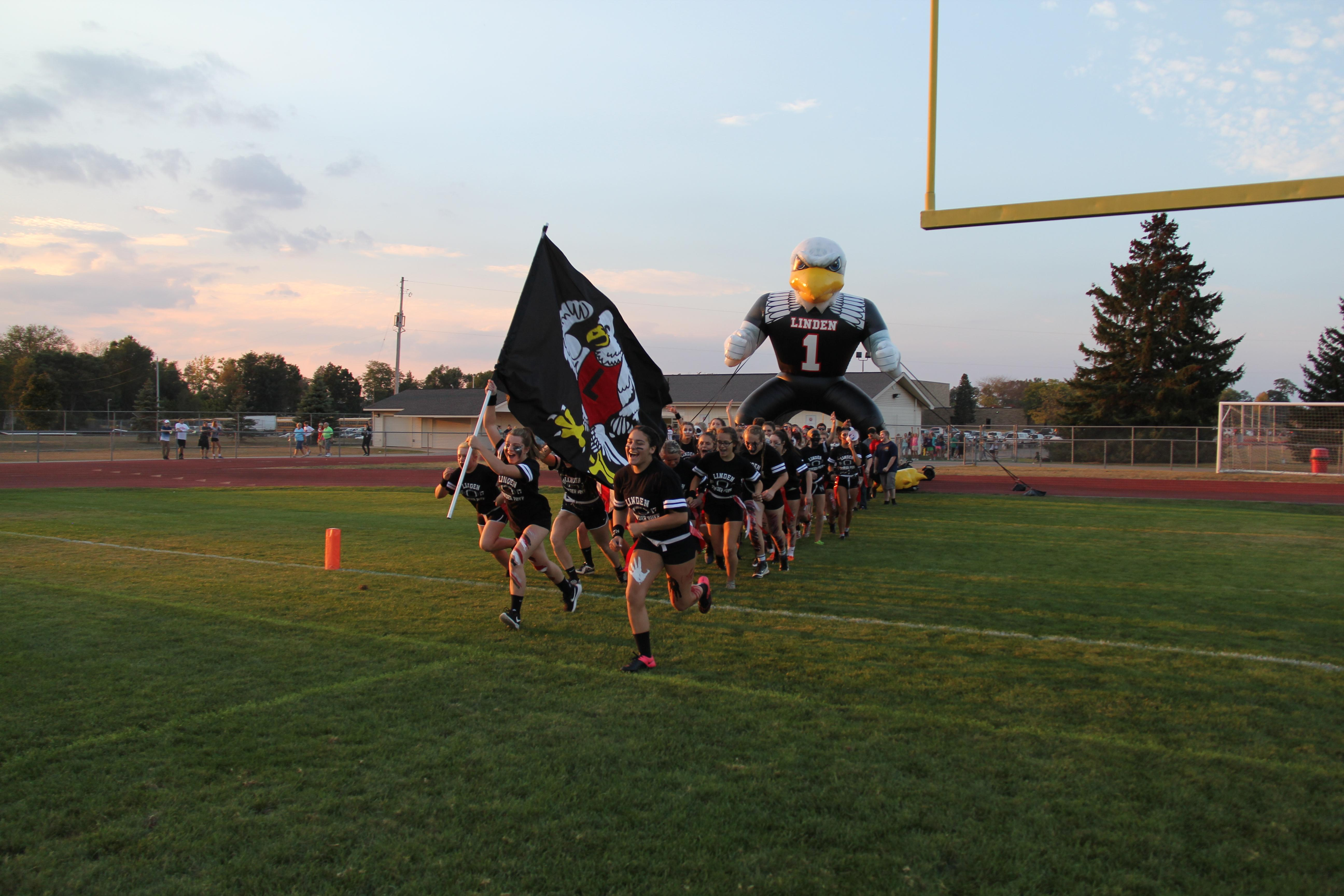 Powderpuff team running onto a football field with a school flag and eagle mascot