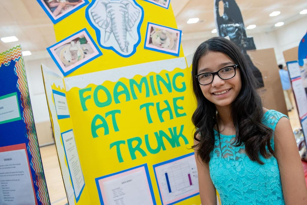 A student stands in front of her project called Foaming at the Trunk