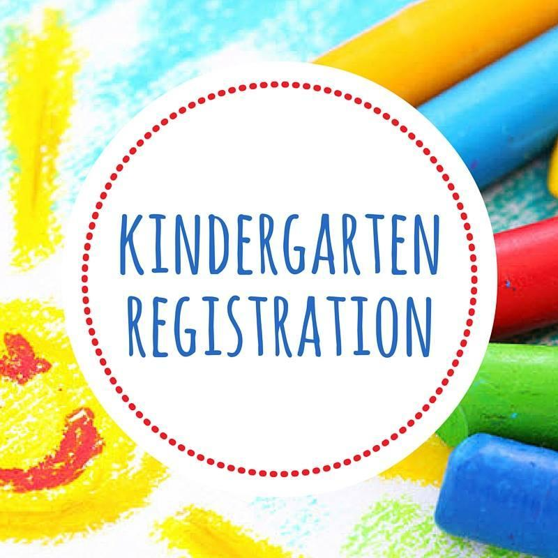 Kindergarten Registration Sign in blue print surrounded by yellow on the left and blue, red, and green chalk on the right