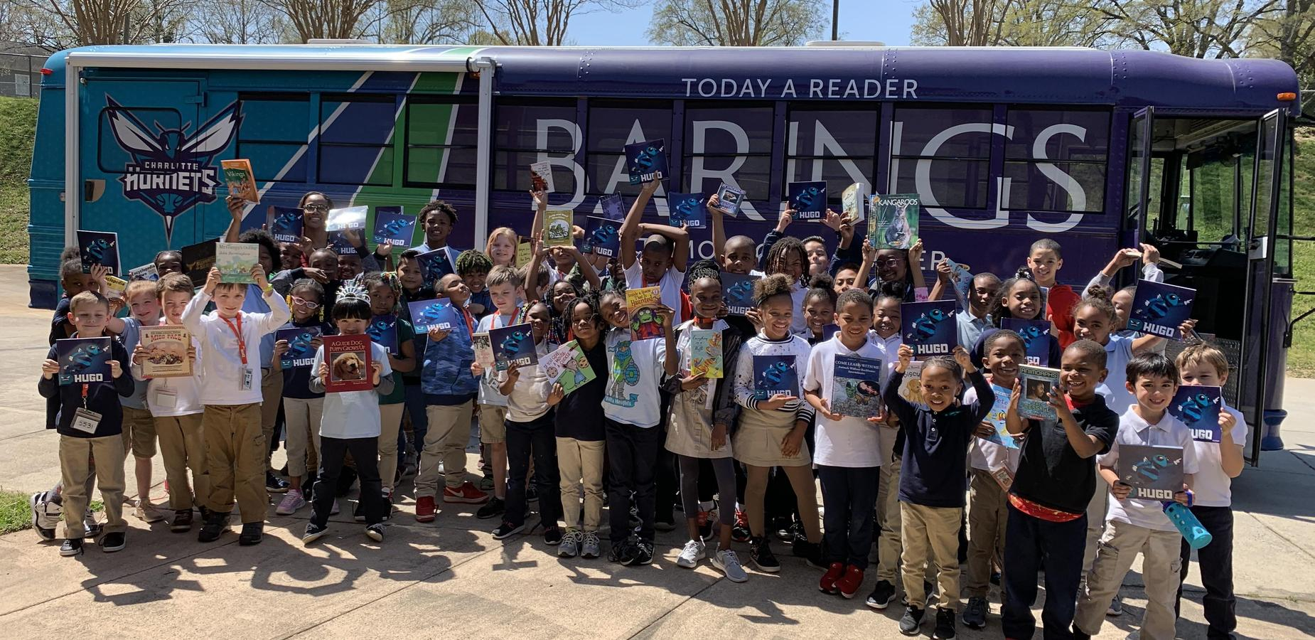 Students standing in front of Barings Book Bus holding books.