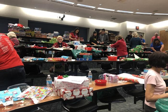 Volunteers wrap gifts for students.
