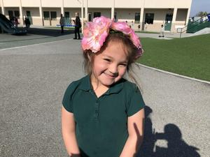 A kinder student showing off her flower hair