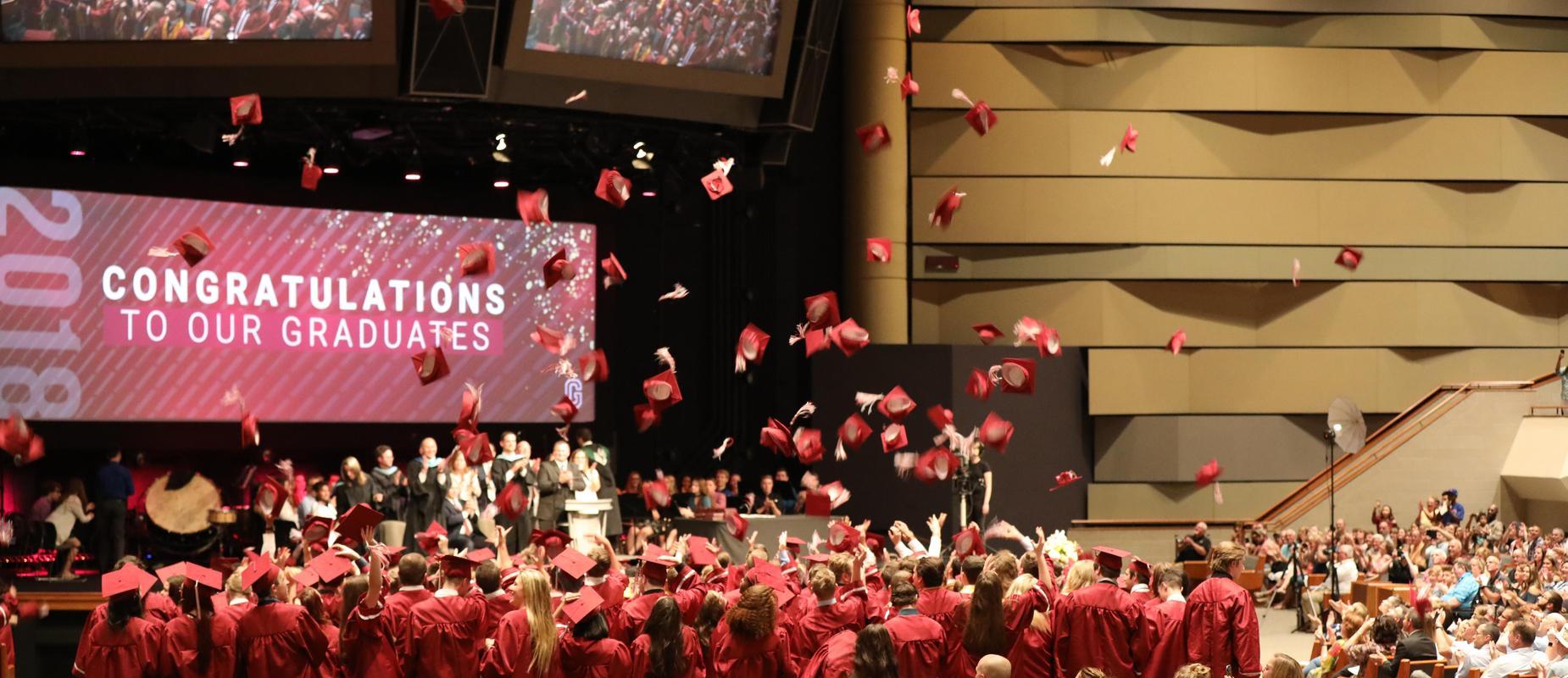 grads throw their maroon caps in the air at graduation