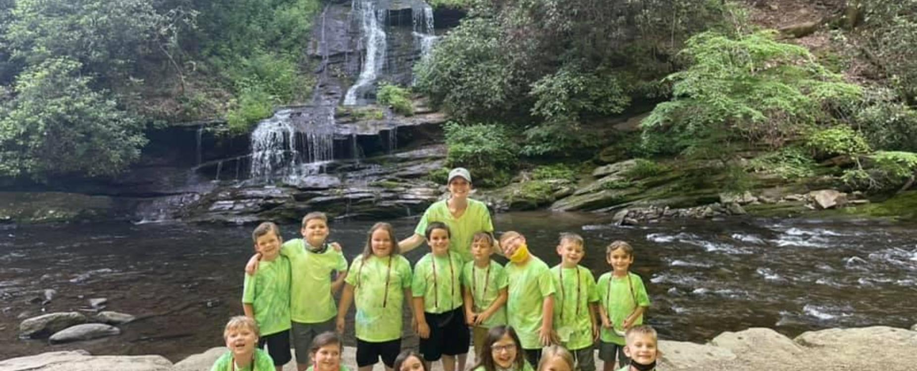 Class in front of waterfall