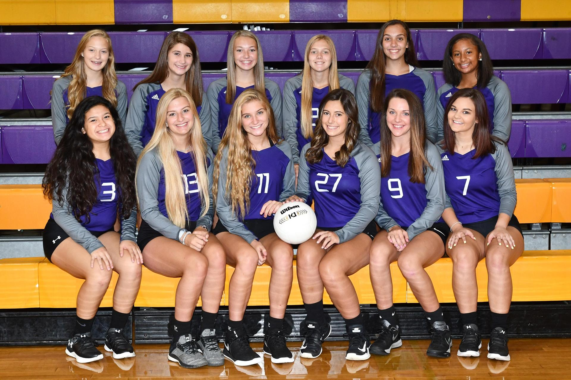 The Varsity Volleyball team poses for a team picture on purple and gold bleachers