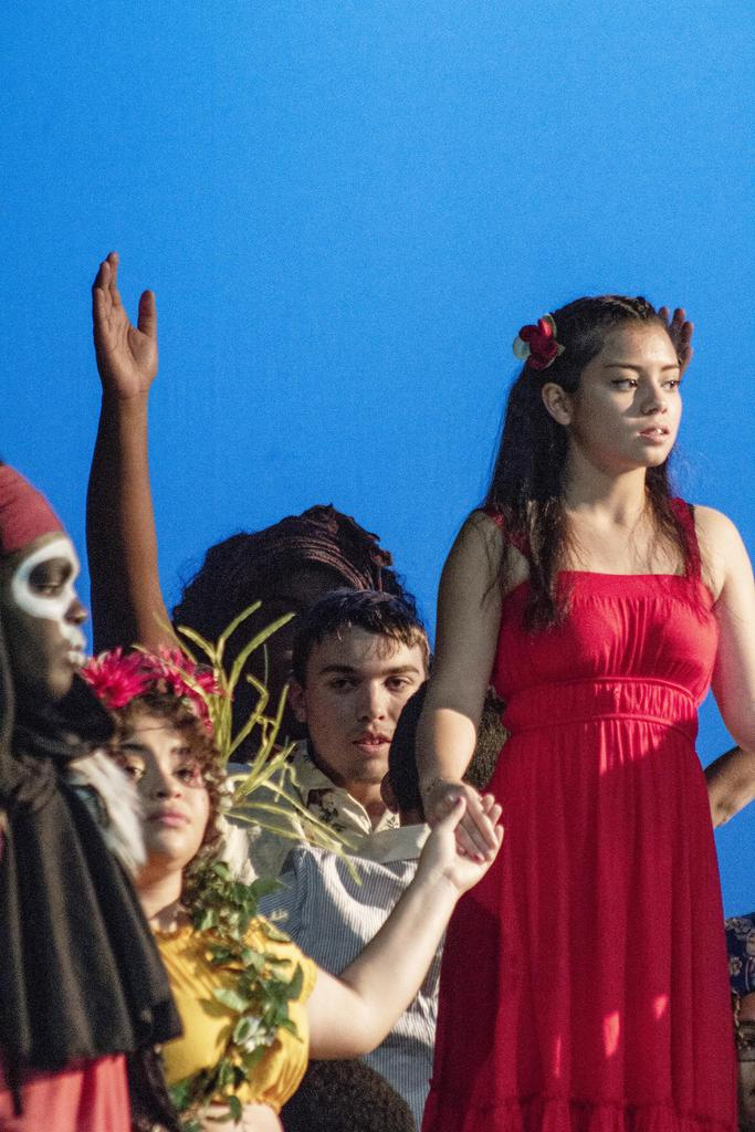 A close-up of four students on stage, each looking at a different point in the audience