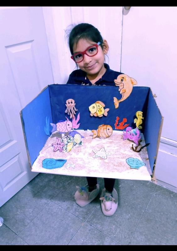 Girl wearing glasses holding her ocean project