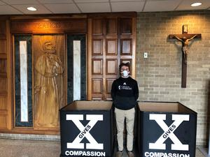 Ian Domeika '21 in front of food collection boxes at Xavier.er