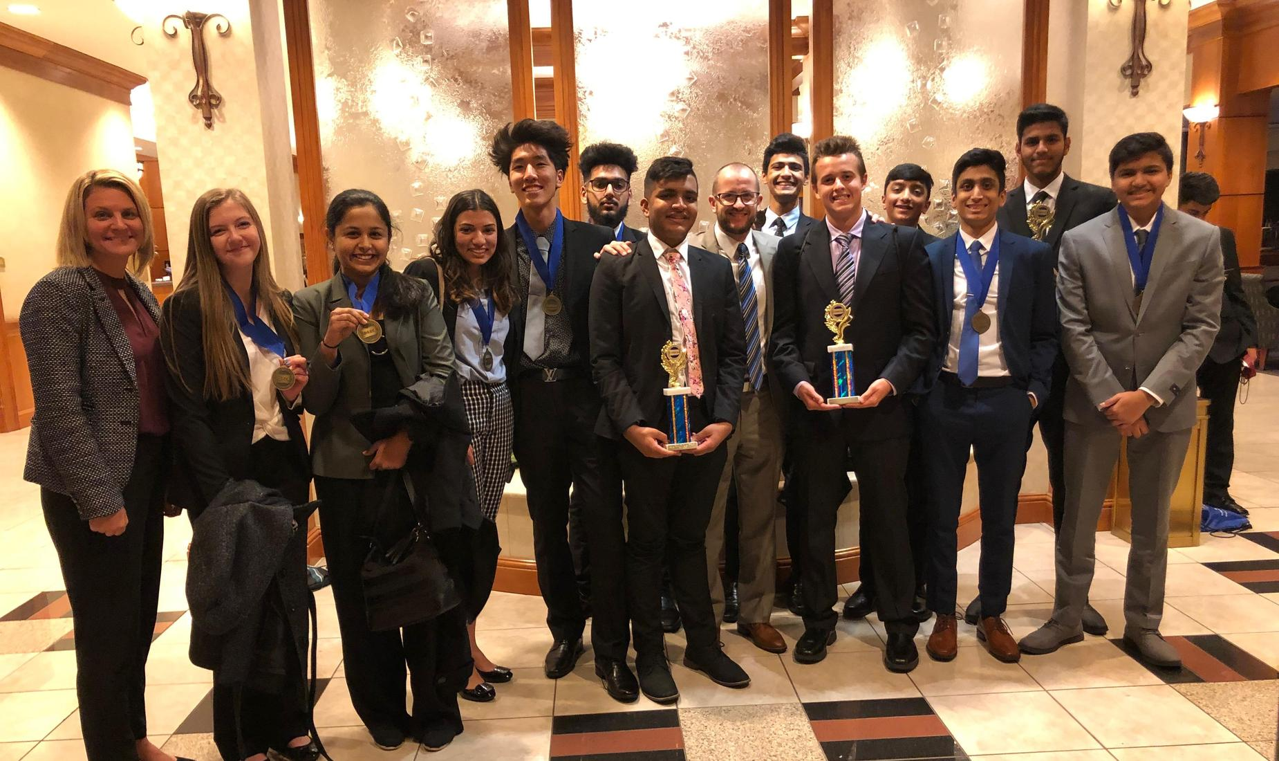 12 DECA students, 9 boys and 3 girls, holding trophies they won at the District DECA competition.