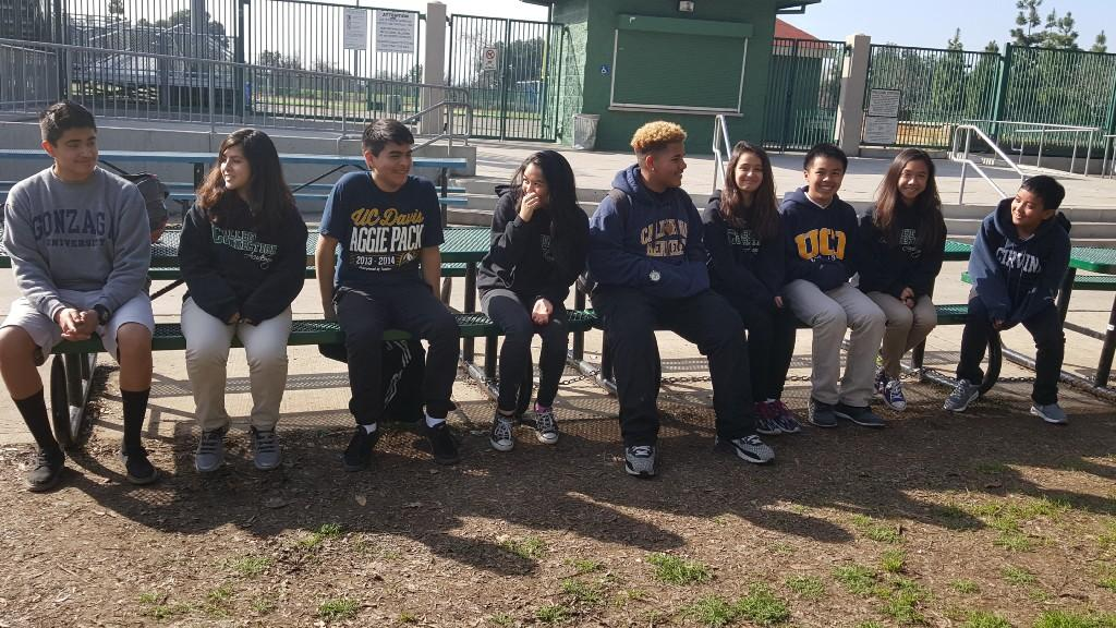 Group of students sitting on bench together.