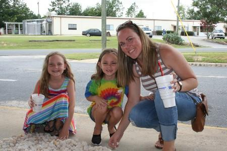 A parent is helping student's choose rocks to paint for Tifton Rocks.