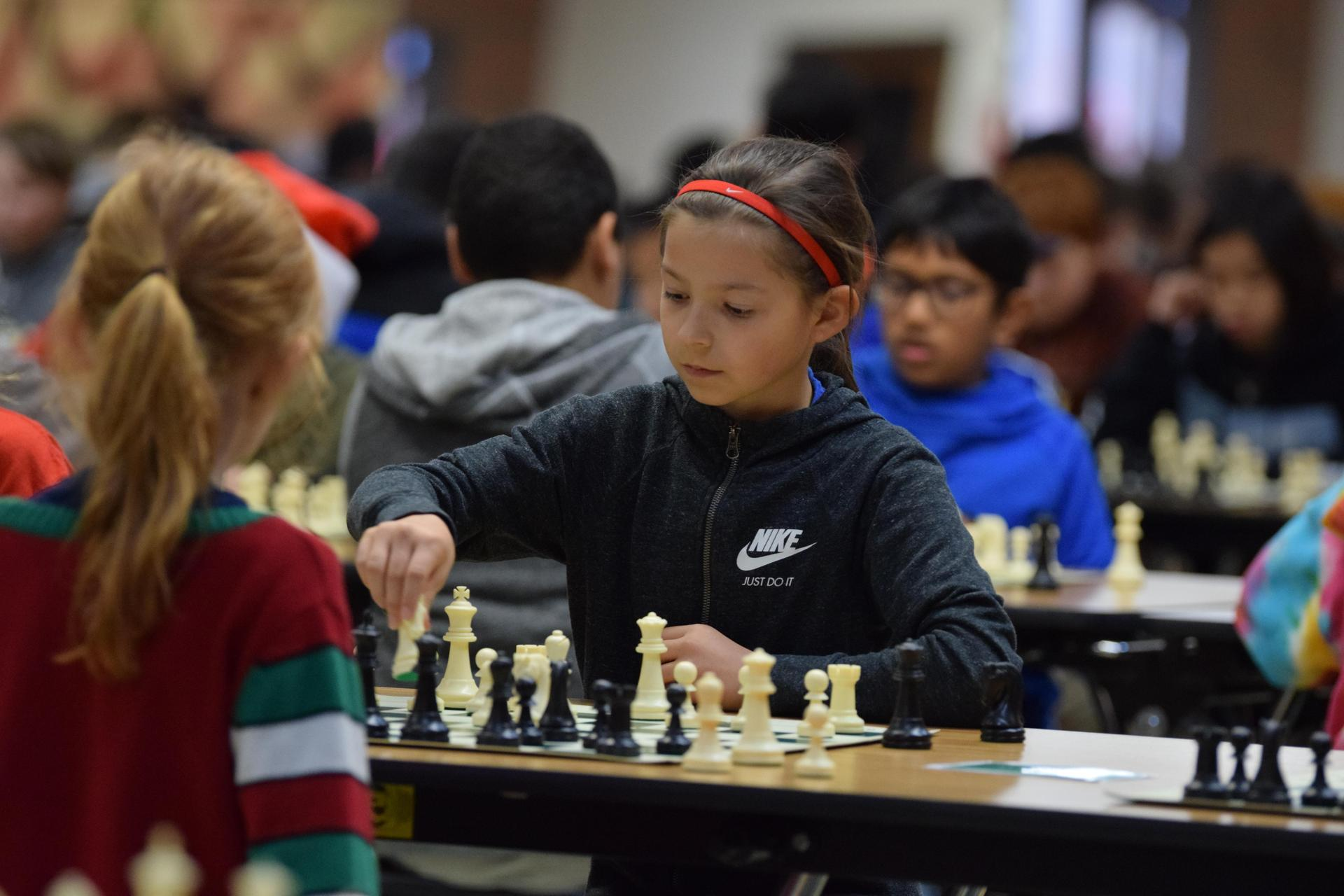 young girl making a move in chess
