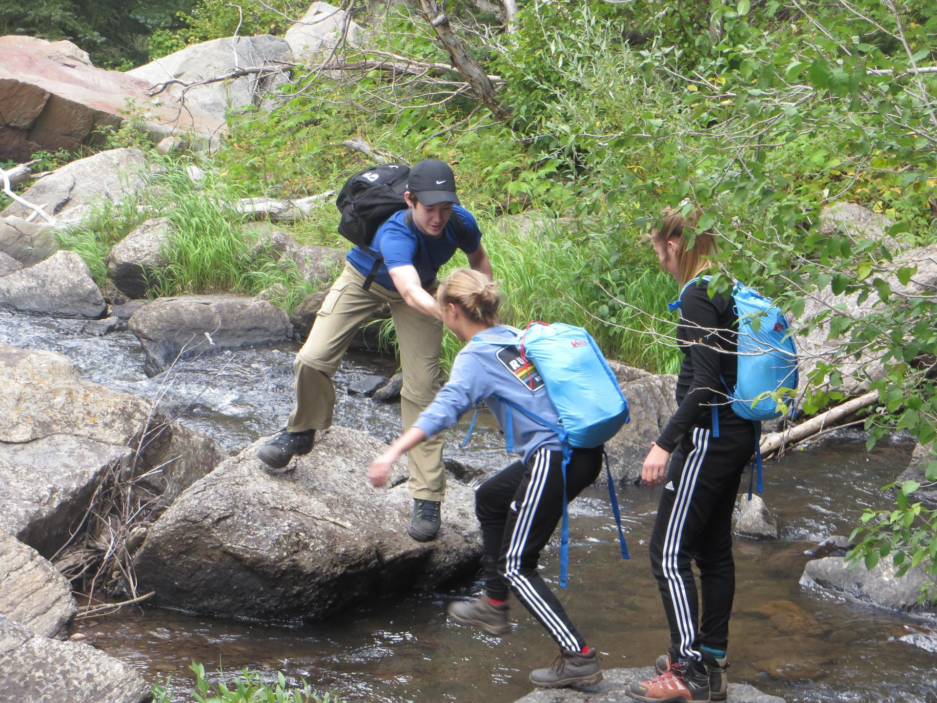 One student helps two others cross a stream