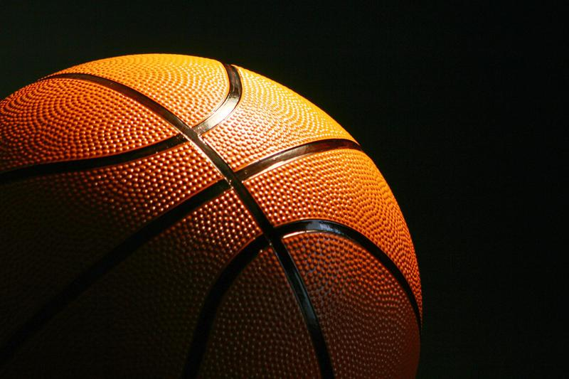 Closeup of a basketball, partly in darkness