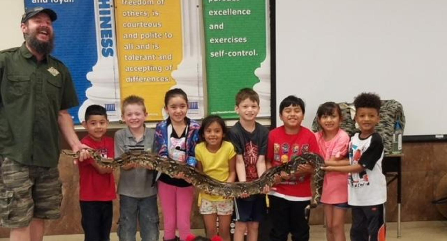 Cypress students holding a large snake at a school assembly with the help of a trained professional