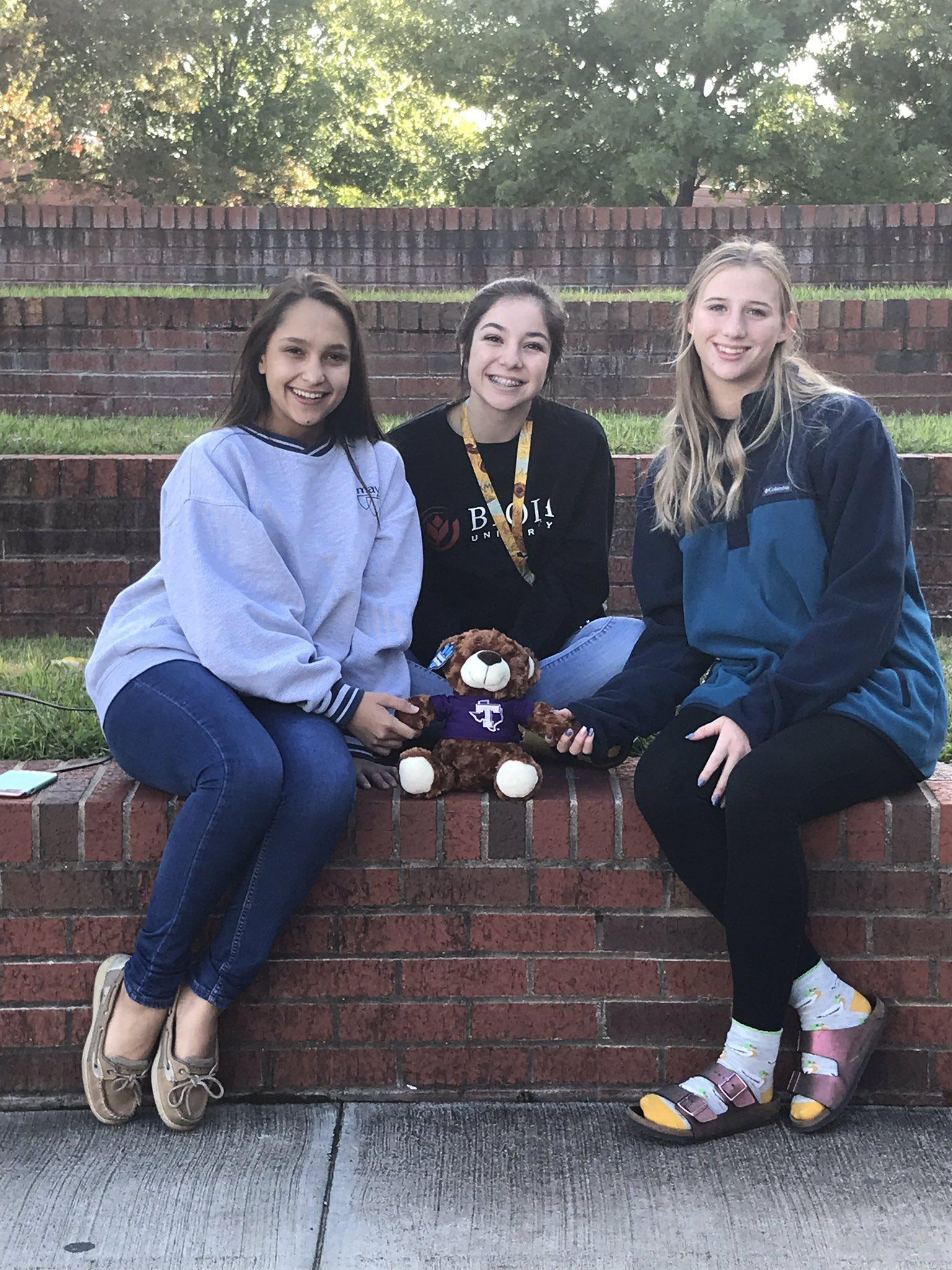 three students with teddy bear sitting outside on a brick wall