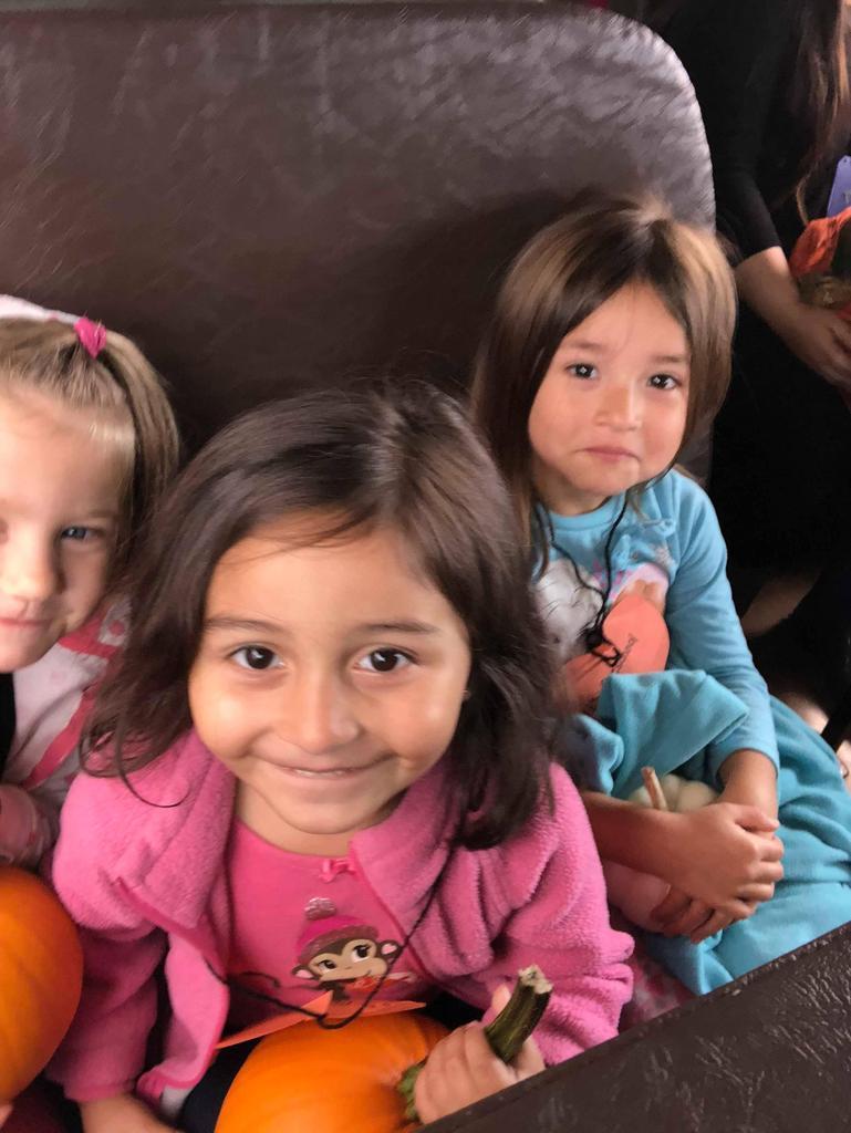 3 children sitting on a school bus