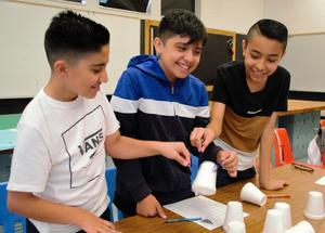 Seventh-graders from Jones Junior High School work on a teambuilding and science, technology, engineering and mathematics (STEM) challenge that tasked students with stacking cups using only rubber bands on the first day of school on Aug. 15.