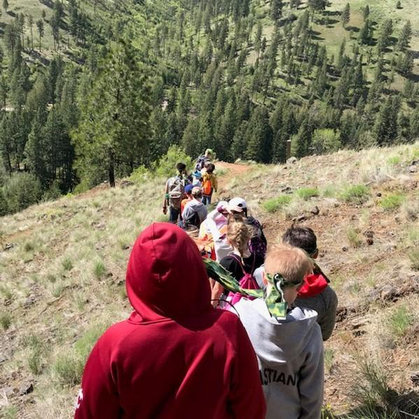 birds eye view of students walking down a mountain trail