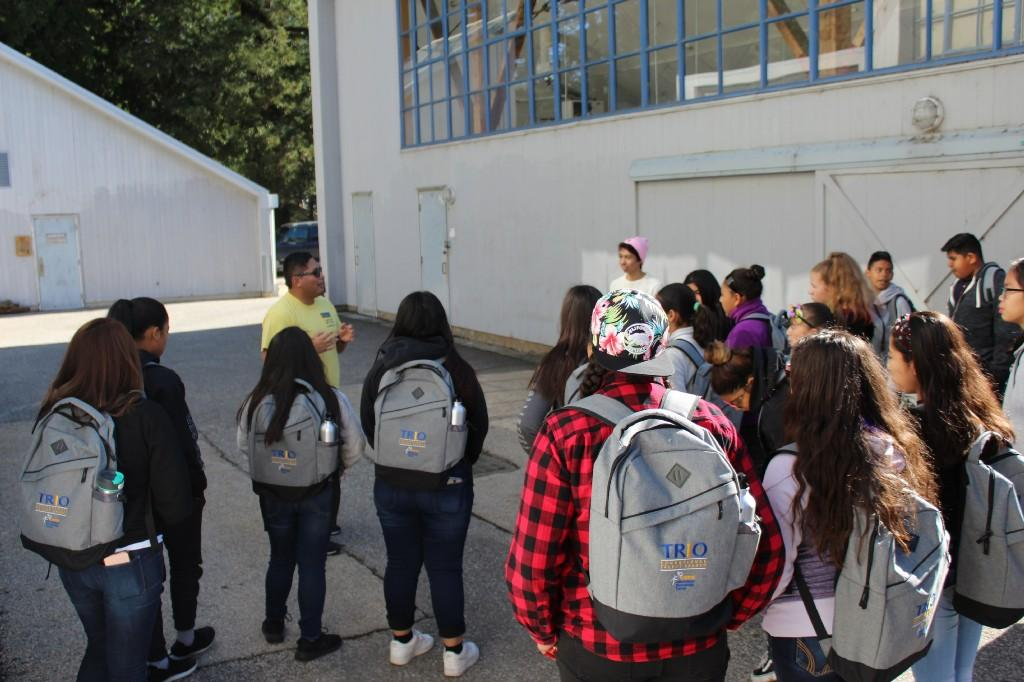 several students next to a building listening to a group tour leader at UCSC
