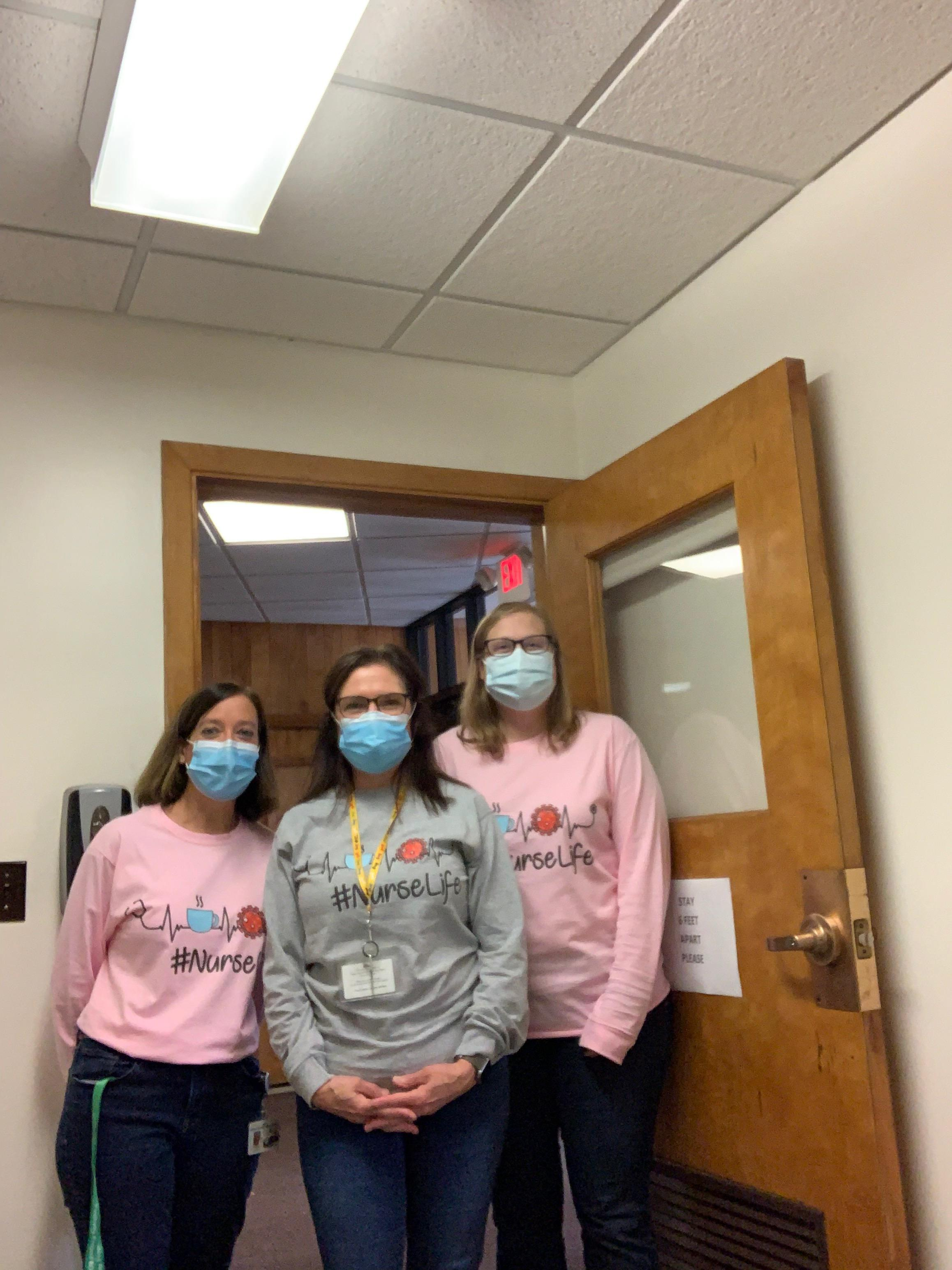 Three school nurses in masks stand for a photo