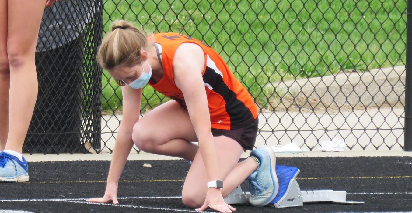 Girl's track team member gets ready in the starting blocks.