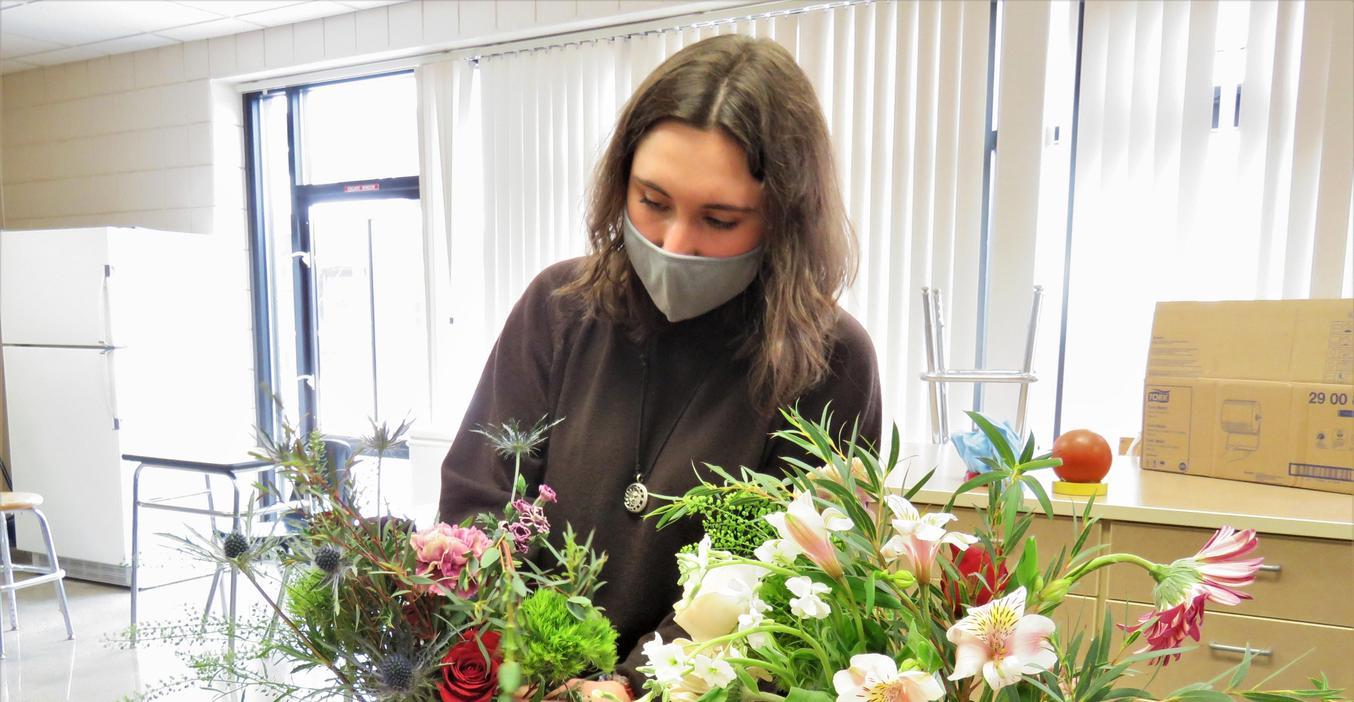 A student works on a flower arrangement.