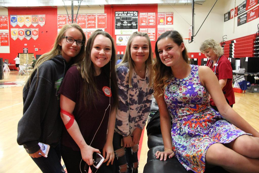 Four smiling students donating blood