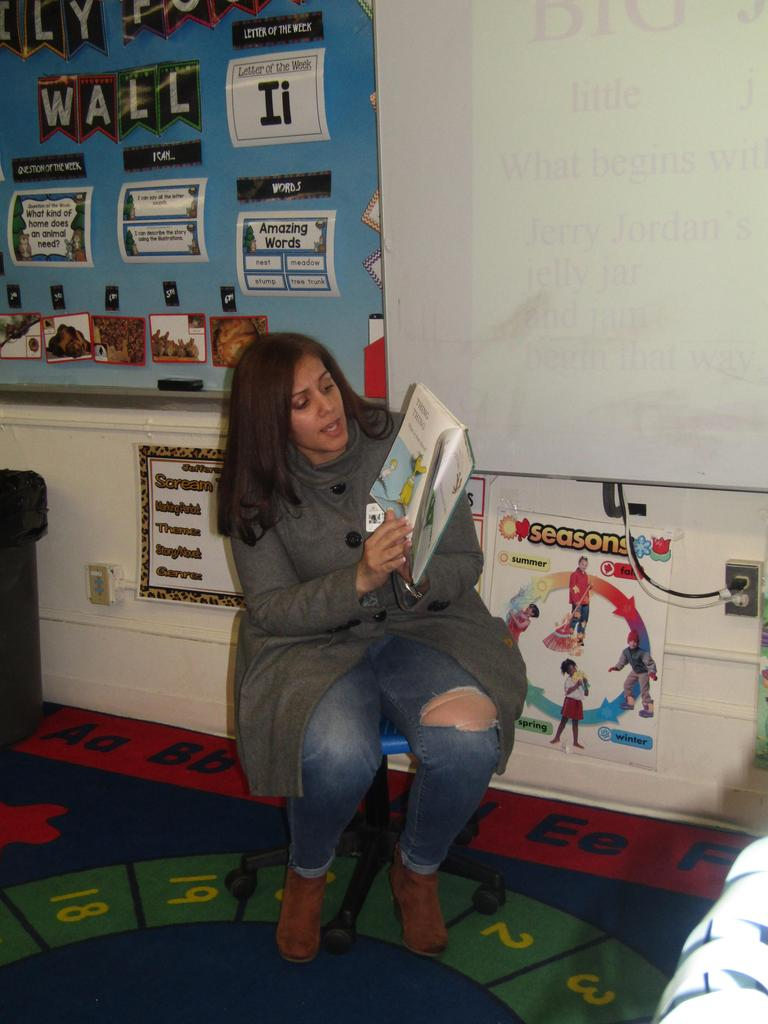 mother reading book aloud to the class