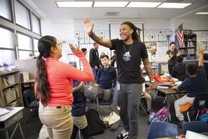 Shavonte Zellous gives a high-five to Jefferson Elementary School student