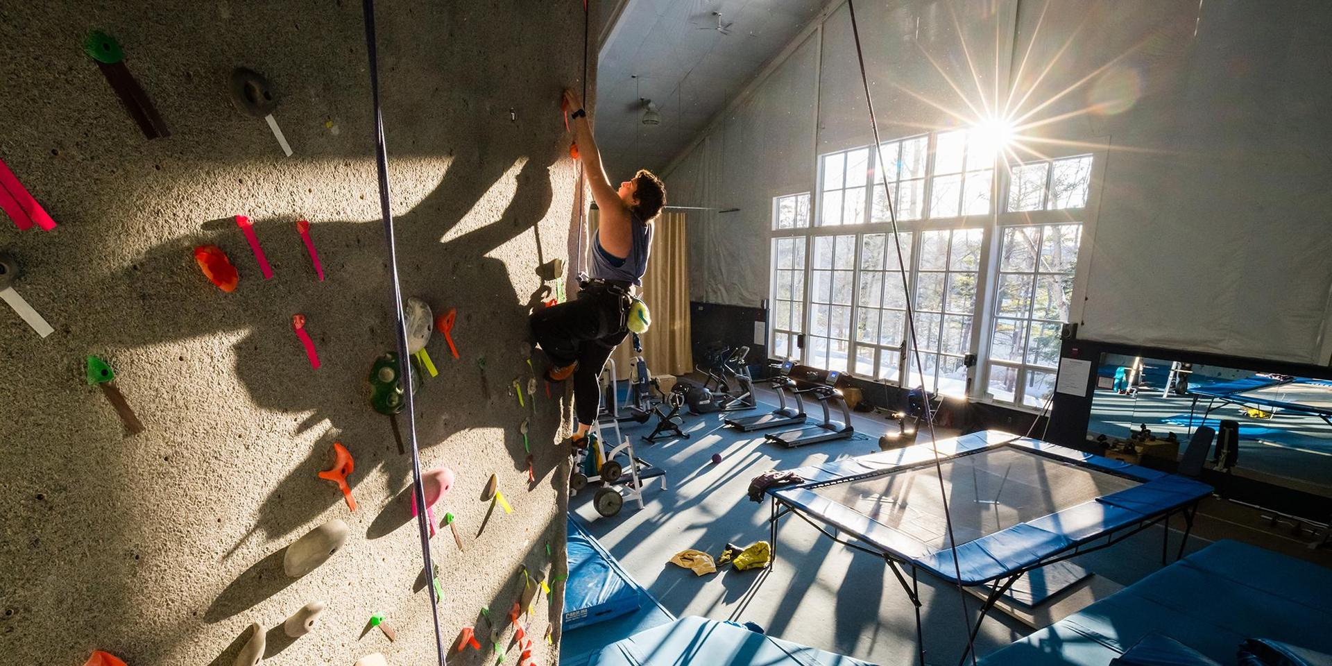 A student climbing on the Beverly Selinger Buder Climbing Wall.