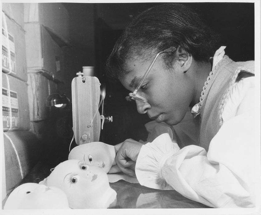Female student using a sewing machine to sew a doll head on fabric.