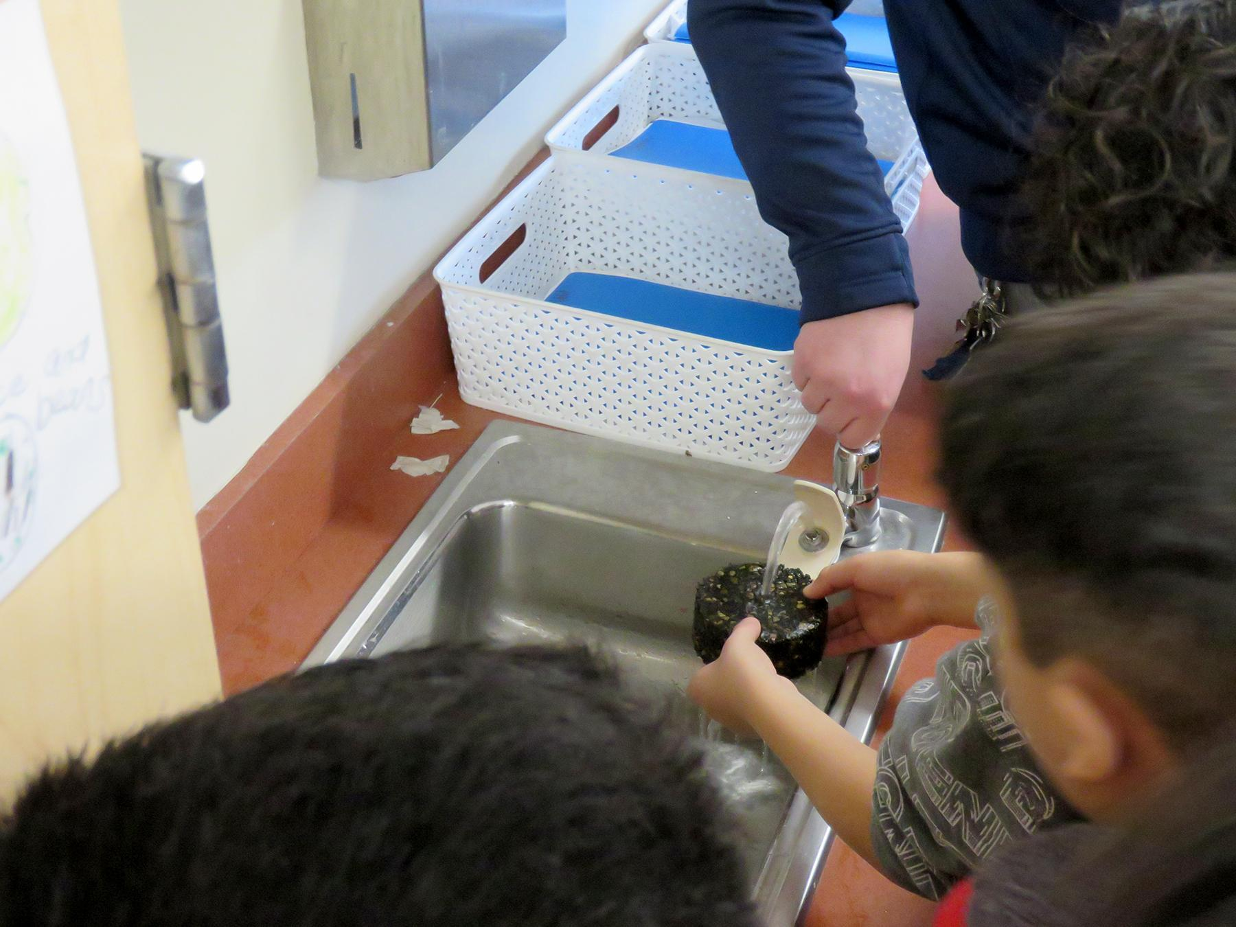 Students test a product under running water