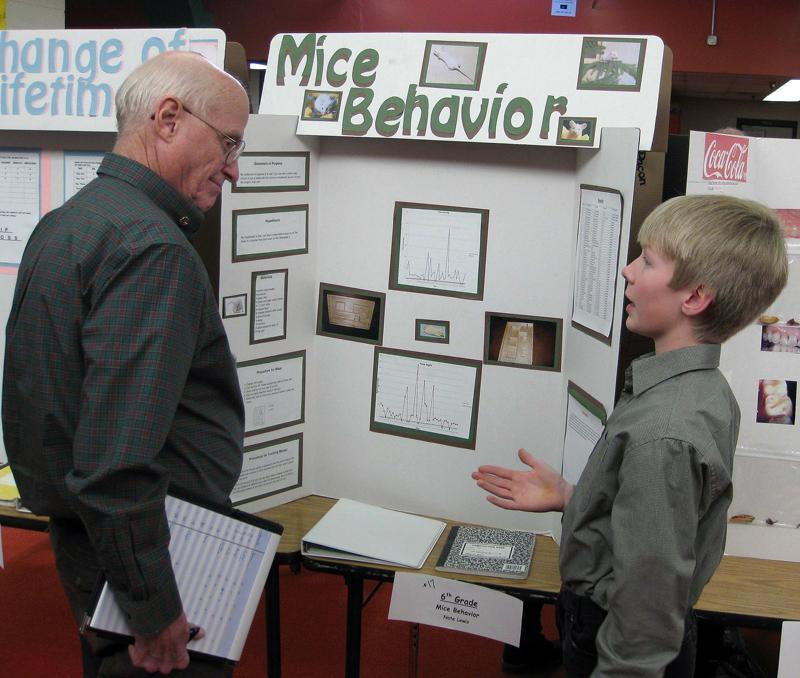 science fair judge talking to a student in front of a science fair board