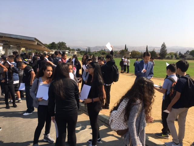 teacher and students in a field looking at image of the solar eclipse on paper in their hands