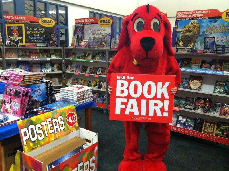 Picture of real book fair with Clifford the dog holding a sign that reads