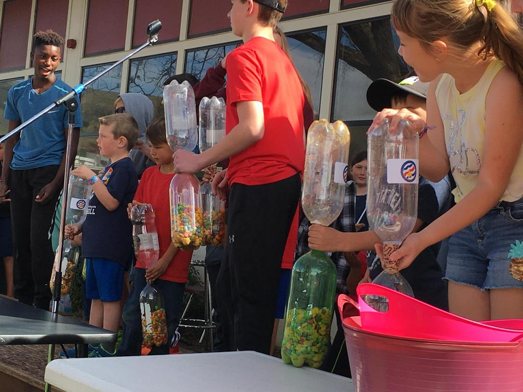 students shaking bottles at assembly