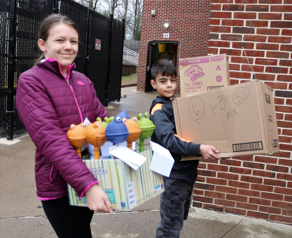 Photo of two Franklin students carrying boxes of toys